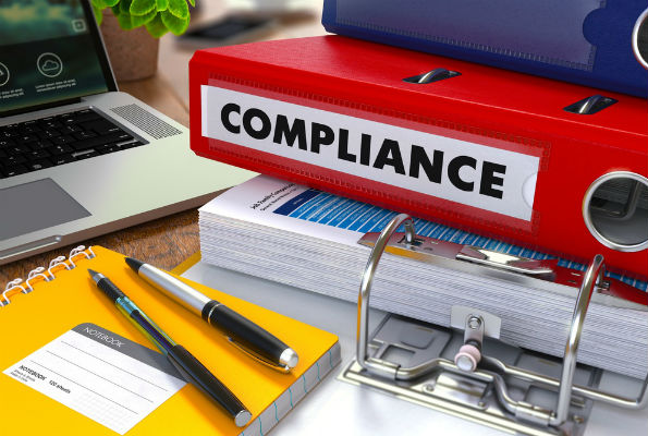 "Image of binder labeled ""compliance"""